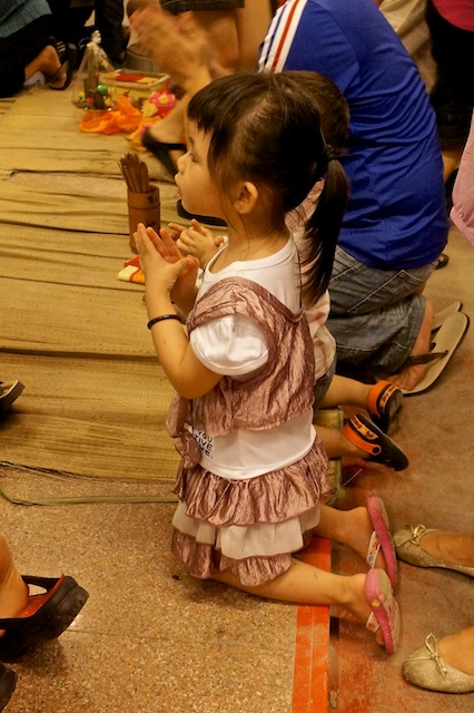 girl kneeling at prayer in Chinese temple Kuala Lumpur