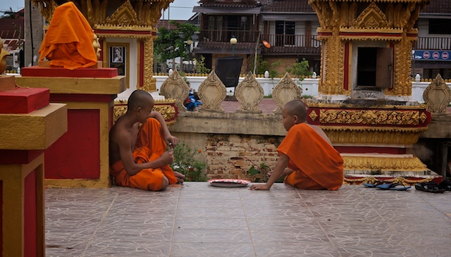 Novice monks by the head of the reclining Buddha image in Vientiance