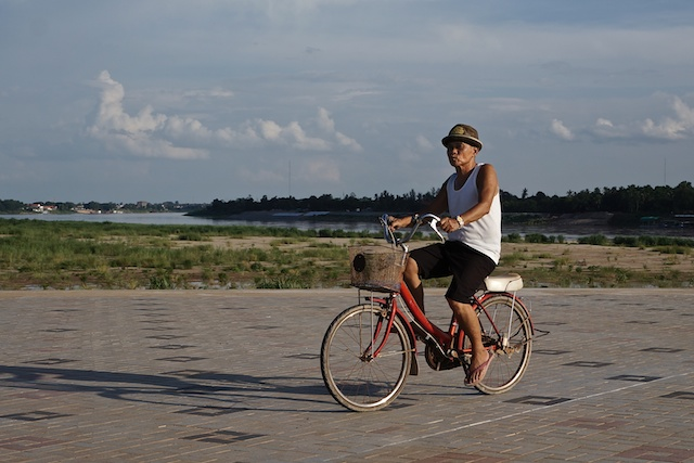 Vientiane, by the Mekong river in Laos, older man riding a bike