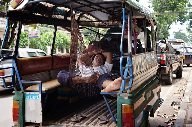 Tuk tuk driver in a hammock asleep