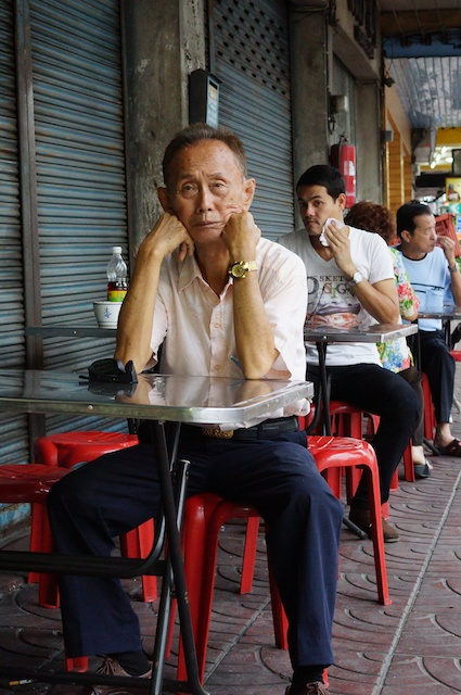 man waiting for food at a street cafe in Chinatown, Bangkok