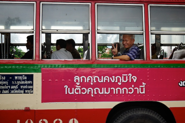 Smiling man doing a peace sign on a pink bus
