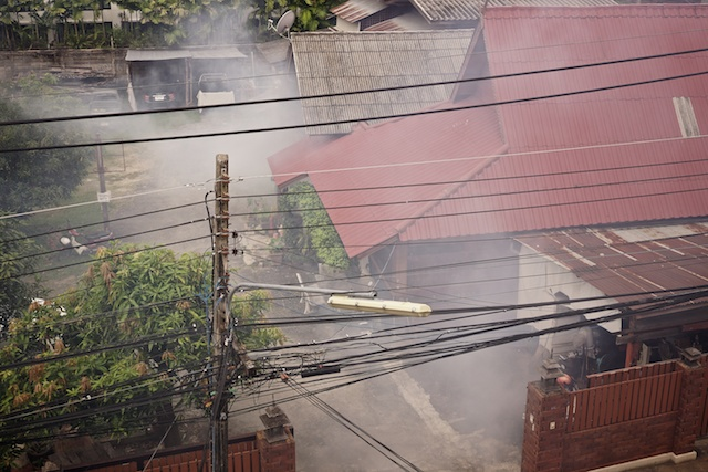 buildings in anti mosquito spray clouds of smoke