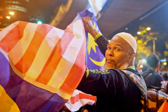 Man with Malaysian flag at Turun Rally in KL on NYE 2013