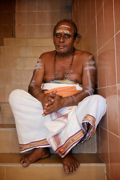 Hindu man sitting in a temple - Tahipusam 2014