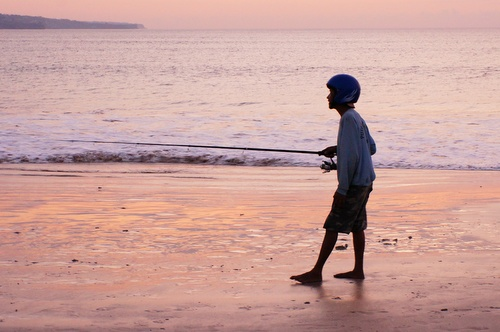 Fishing in a Helmet on Bali beach at Sunset