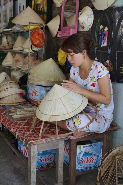 Bored lady making a conical hat in a village outside Hue, VIetnam