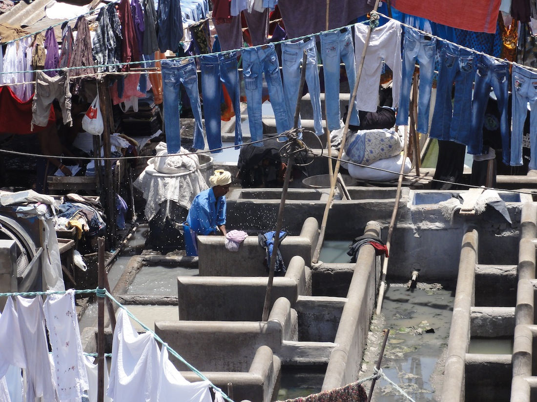 man washing jeans at Dhobi Ghat