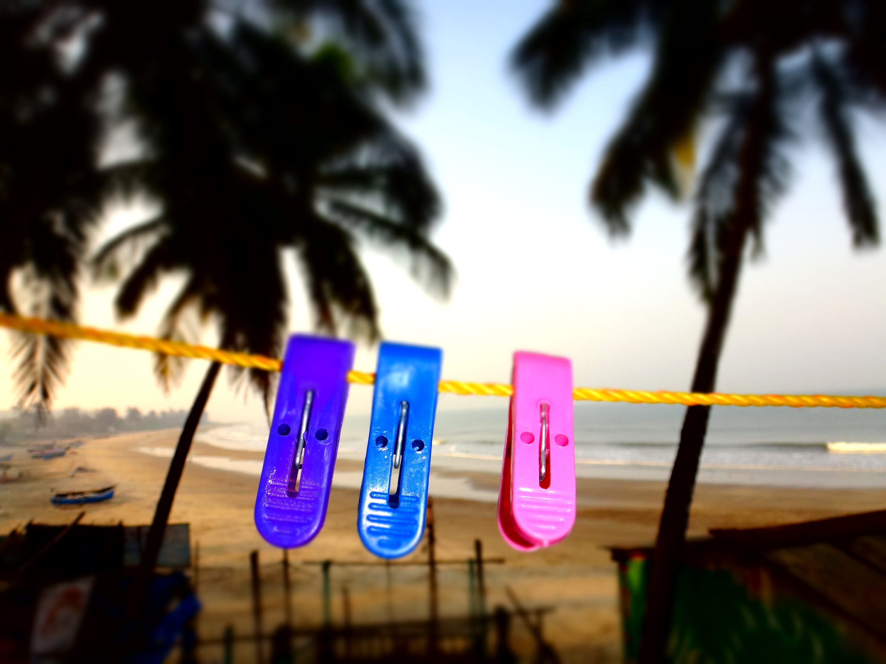 colourful pegs on a line with beach in soft focus in background