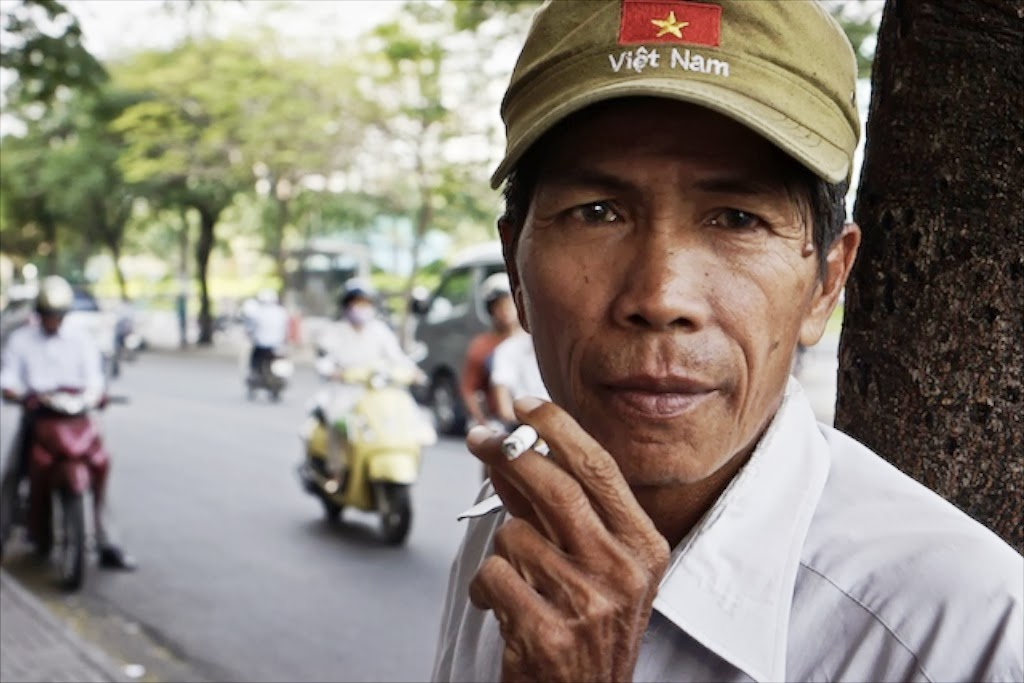 Vietnamese man wearing Vietnam hat smoking a cigarette