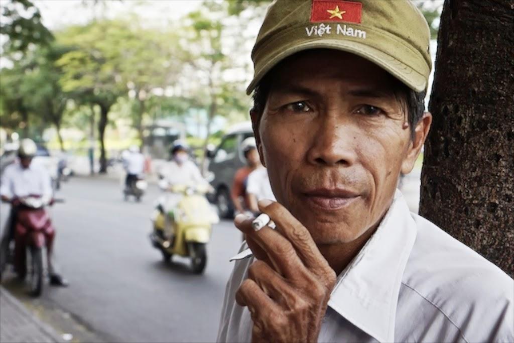Vietnamese man wearing Vietnam hat smoking a cigarette