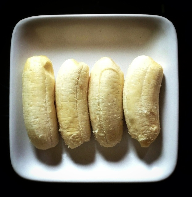 4 small peeled bananas on a plate