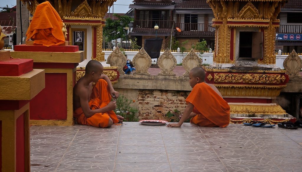 Two monk boys talking at the reclining Buddha in Vientiane