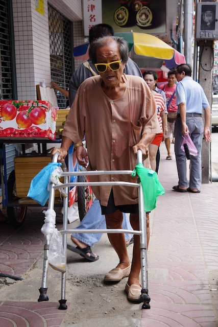 Man with a walking frame and bright yellow sunglasses