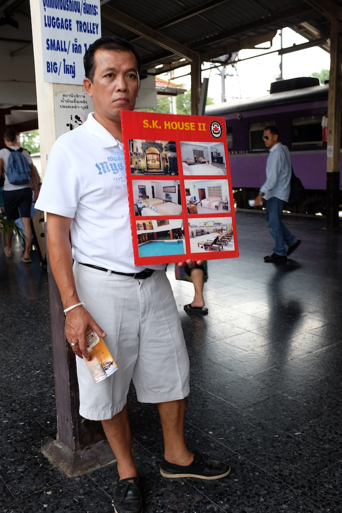 man holding sign at Chiang Mai train station