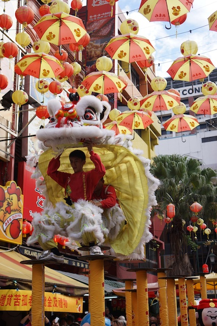 lion dance on poles Chinatown, KL at winter solstice