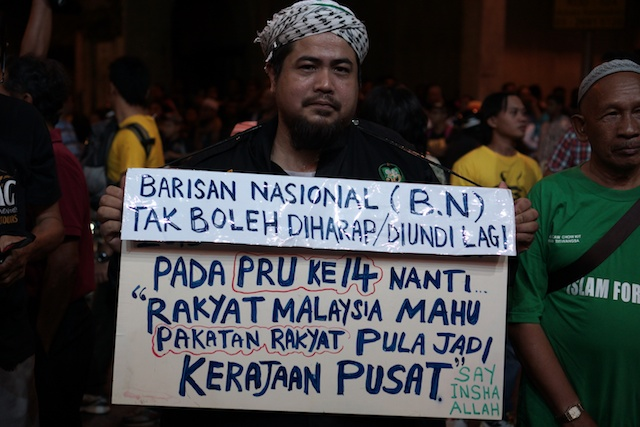 Turun protester with sign at KL NYE rally