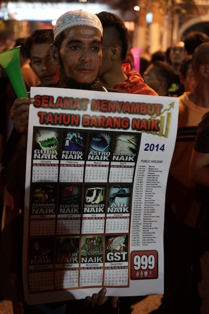 Protester holding a sign with information on what will rise in price during 2014 at Turun Rally in KL 31.12.2013