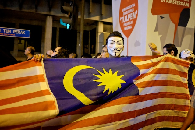 Masked Turun protester with Malaysia Flag