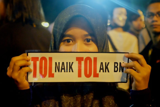 Girl holds sign protesting the rise in road tolls at the Turun rally in KL on 31.12.2013